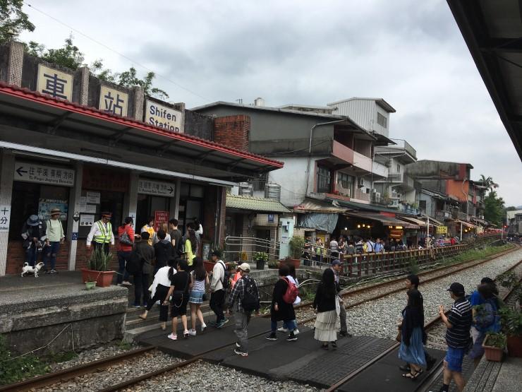 台湾 十分駅、商店街(十分老街)すれすれに電車が走る